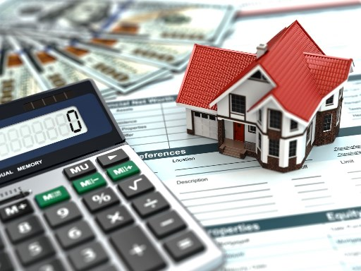 Picture of home sitting on a calculator and spreadsheet